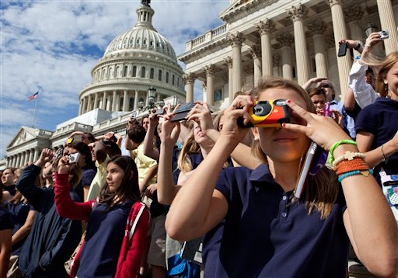 Sixth-graders visiting the Capitol from from the Stratford Academy in Macon, Ga., watch the final voyage of the space shuttle Discovery as it soars above Washington after a flight from Cape Canaveral, Fla., Tuesday, April 17, 2012. Discovery, the world's most traveled spaceship, now becomes an attraction at the Smithsonian's National Air and Space Museum's Stephen F. Udvar-Hazy Center in Chantilly, Va., next to Dulles International Airport. (AP Photo/J. Scott Applewhite)