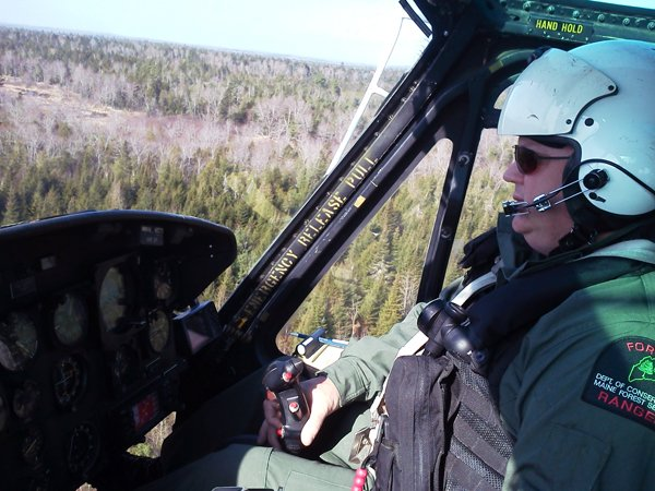 Ranger Chris Blackie pilots a Maine Forest Service helicopter over woods in Howland, where the search continues for Dean Levasseur, who has been missing since Saturday.