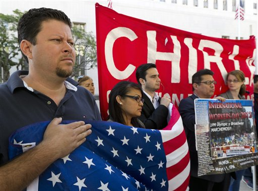 Raul Murrillo director of Hermandad Mexicana Nacional, left, joins the Coalition for Humane Immigrant Rights of Los Angeles during a vigil outside Los Angeles Federal court to denounce Arizona's immigration enforcement on Tuesday.