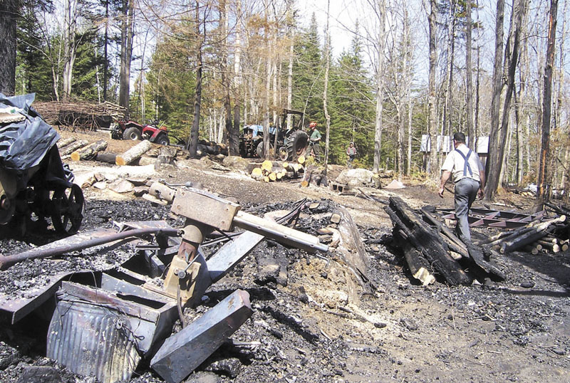 REMAINS: Donald Smiley Jr., 72, cleans up the charred remains of his family-owned sawmill, which was destroyed by a fire early Saturday morning. Smiley recently handed over the business he and his wife Pamela started 32 years ago to their son, Brian, who plans to rebuild the uninsured mill off Knowlton Corner Road.