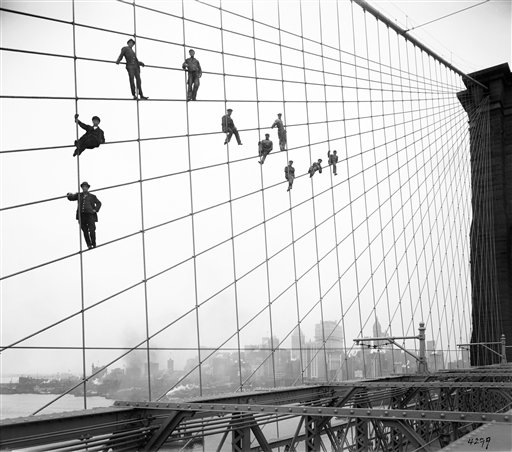 In this Oct. 7, 1914, photo, painters are suspended from wires on the Brooklyn Bridge in New York.