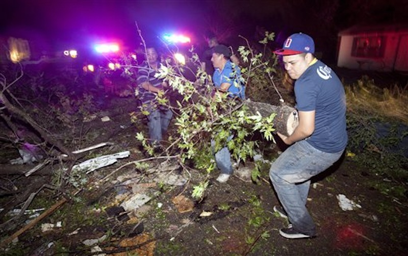 Residents of a south Wichita neighborhood clean up fallen trees after a tornado caused massive destruction in the Wichita, Kan.-area on Saturday night, April 14, 2012. (AP Photo/The Wichita Eagle, Travis Heying)