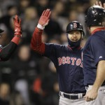 Cody Ross, center, celebrates with Kevin Youkilis, right, and David Ortiz after scoring on a three-run double by Darnell McDonald in the sixth inning of the Boston Red Sox game against the Chicago White Sox in Chicago on Friday.