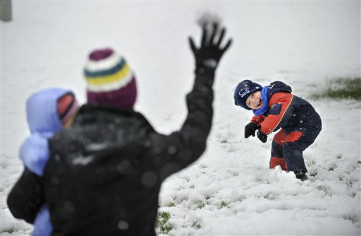 Evan Dreibelbis, 3, tries to avoid a snowball during a snowball fight in fresh snow in their front yard with his mother Dana Dreibelbis and sister Elle today in Pine Grove Mills, Pa.