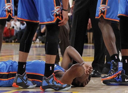Oklahoma City Thunder players stand over teammate James Harden after he received a flagrant double foul from Los Angeles Lakers' Metta World Peace, who was then ejected. The incident took place in the first half of a game on Sunday in Los Angeles.
