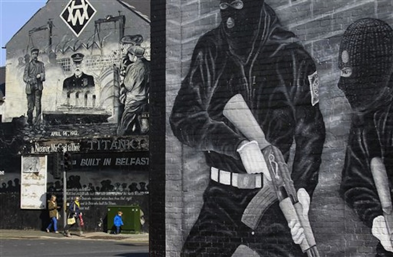 People walk past a Titanic mural in the Loyalist Newtownards Road area of East Belfast, Northern Ireland, Friday, April 13, 2012. (AP Photo/Peter Morrison)