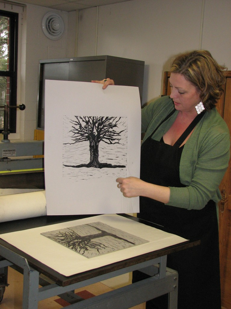 "Hosanna Jensen, a UMaine-Machias student and member of the design team, studies an image being considered for the cover of ""Julia and the Illuminated Baron."""
