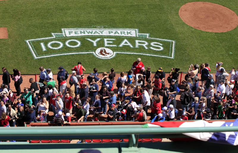 Lines of baseball fans make their way along the infield at Fenway Park in Boston today during an