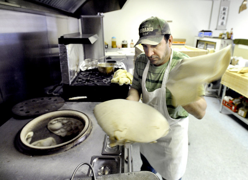 Audai Naser shapes flatbread dough before placing it into the circular tandoor oven to his right.