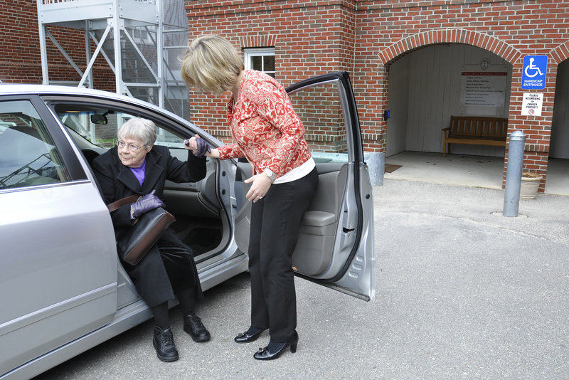 Norma Anderson of Portland is helped out of a car by Kim Savage of ITNPortland, who provided a ride from her home in Portland to Woodfords Congregational Church on Sunday.