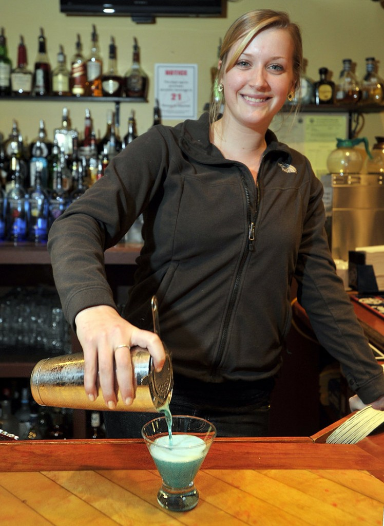 Bartender Sarah O'Neil makes a Blue Melon Martini, one of the Tuesday half-price specials at the Grill House Local Tavern in South Portland.