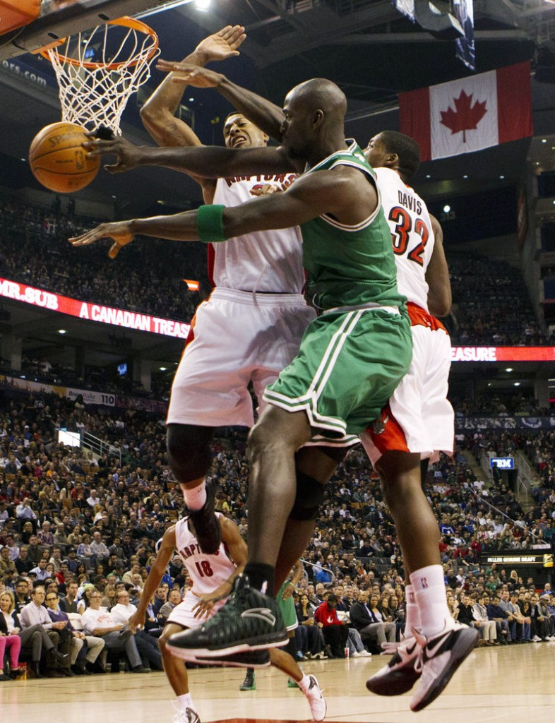 Kevin Garnett of the Boston Celtics finds room to pass Friday night against pressure from James Johnson, left, and Ed Davis of the Toronto Raptors. Toronto won, 84-79.