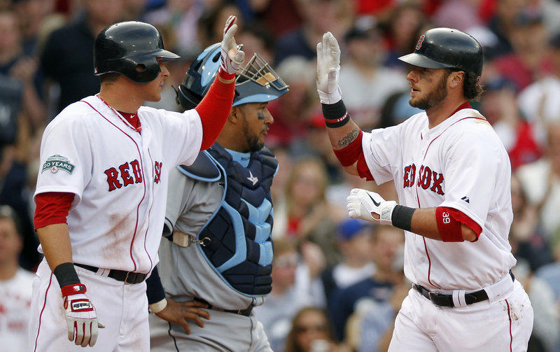 Jarrod Saltalamacchia of the Boston Red Sox, right, celebrates his two-run homer that drove in Ryan Sweeney, left, during the second inning of the 13-5 victory Saturday against the Tampa Bay Rays. The Tampa Bay catcher is Jose Molina.