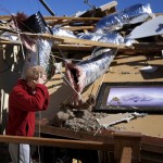 Carole Beckett reacts as she sorts through her belongings Sunday in Woodward, Okla., where five people died in Saturday's tornado. Storms also struck in Kansas, Iowa and Nebraska, but there were no fatalities in those states – thanks to days of urgent warnings, residents and officials say.