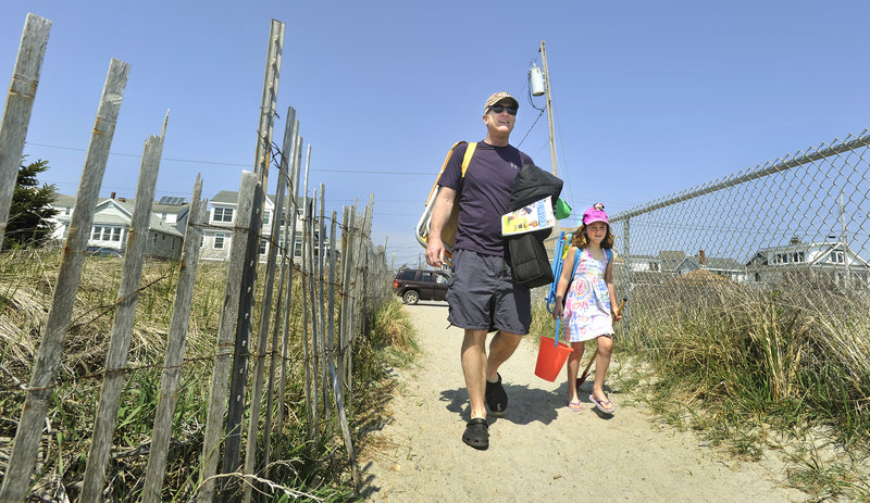 Bill Dwyer of Portland and his daughter Ruby, 5, head for some fun in the sun Monday at Higgins Beach. Dwyer, a frequent beach visitor, said that if the parking fee at Higgins doubled to $10, he would consider paying $65 for a townwide beach parking pass for non-residents.
