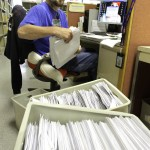 Illinois Department of Revenue office associate Jeff Mumaw processes 2011 income tax forms Monday.