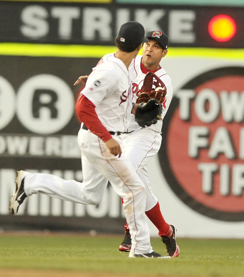 Center fielder Ronald Bermudez of the Portland Sea Dogs pulls in a shallow fly ball Monday night in front of teammate Derrick Gibson in the third inning. The Sea Dogs lost 10-5 to the New Britain Rock Cats in 11 innings.