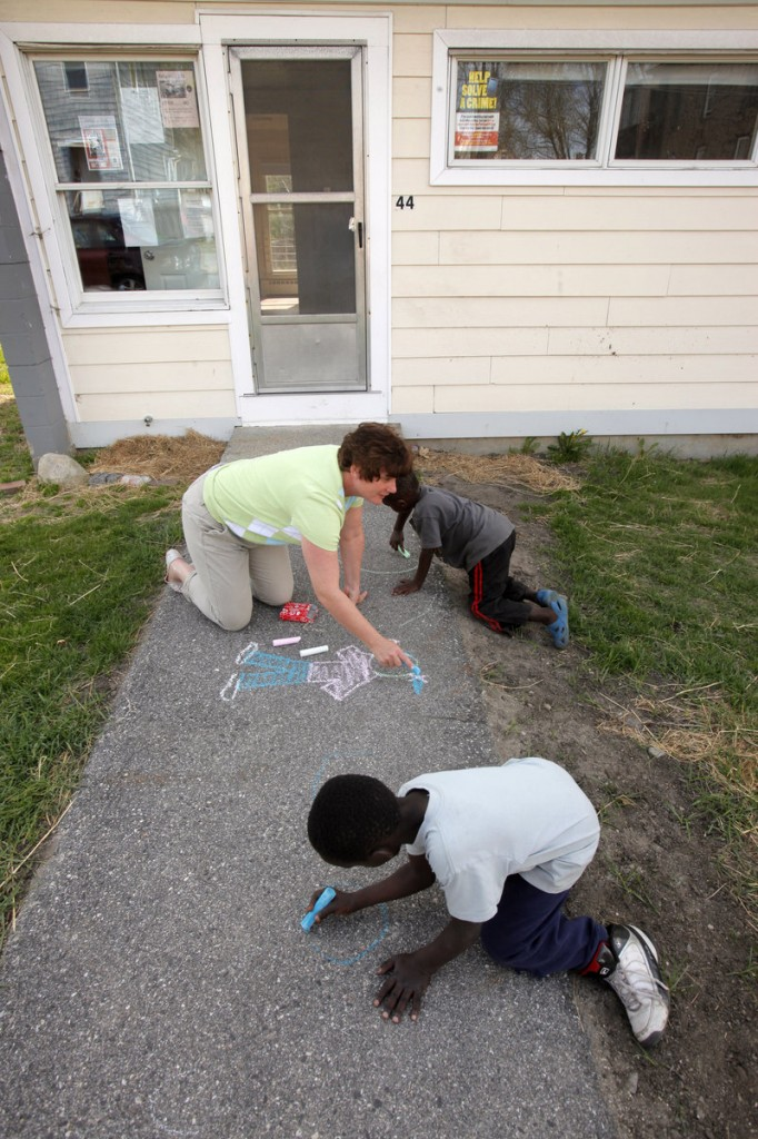 One of the duties of a community services coordinator is getting to know the children and tenants in the neighborhood, as Janine Kaserman was doing Wednesday.