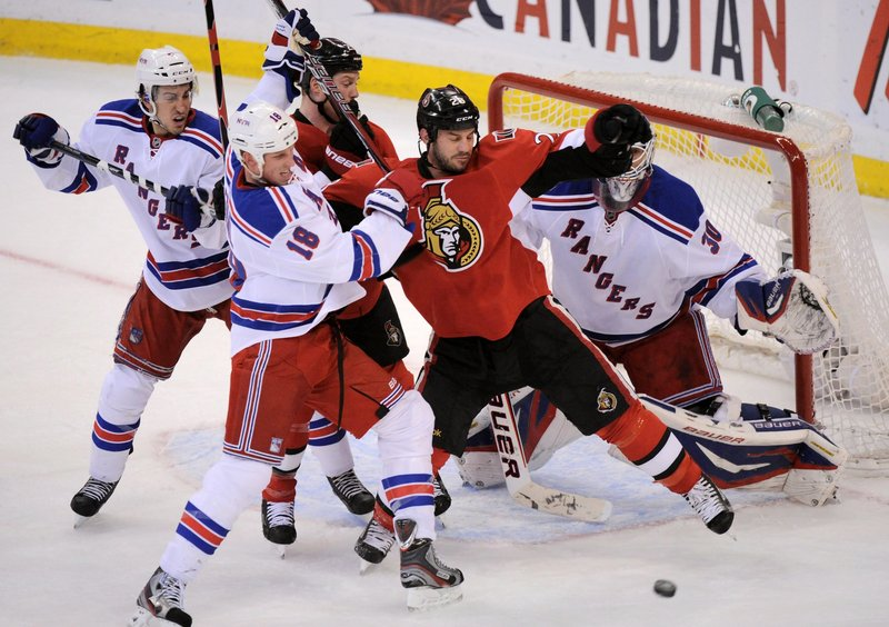 Zenon Konopka of Ottawa battles for position in front of Rangers goalie Henrik Lundqvist while tangling with New York's Marc Staal in Wednesday's game at Ottawa. The Senators won 3-2 in overtime to tie the series, 2-2.