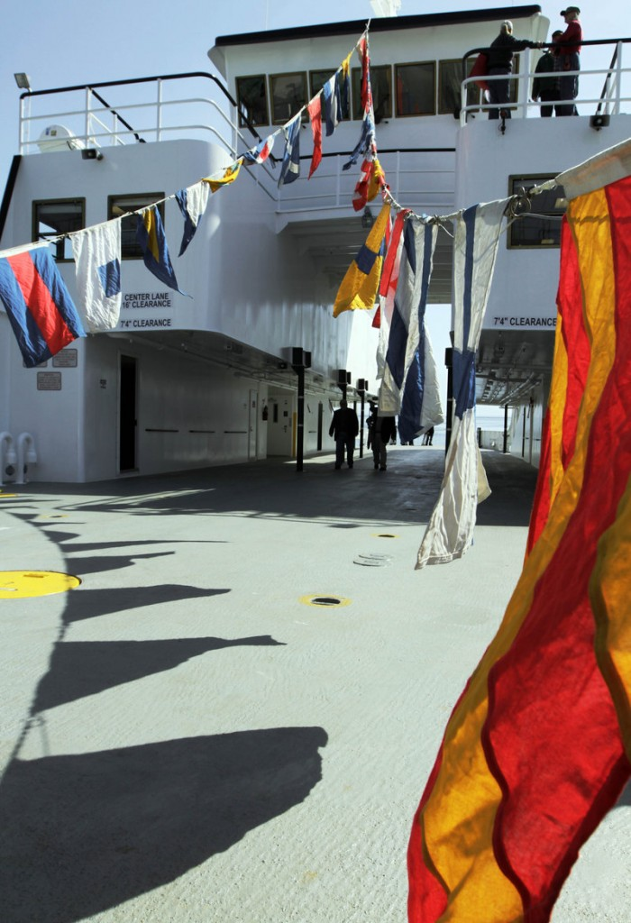 Flags flap in the breeze on the new ferry's deck.