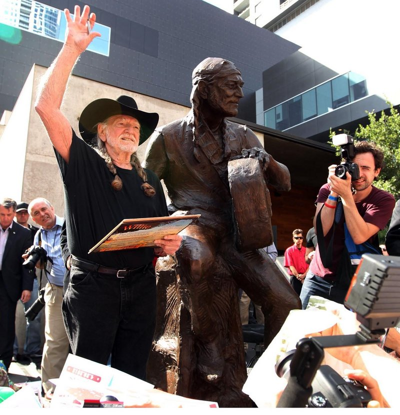 Country singer Willie Nelson waves at the unveiling of an 8-foot-tall statue of himself Friday in Austin, Texas. He also performed with his sister Bobbie Nelson.