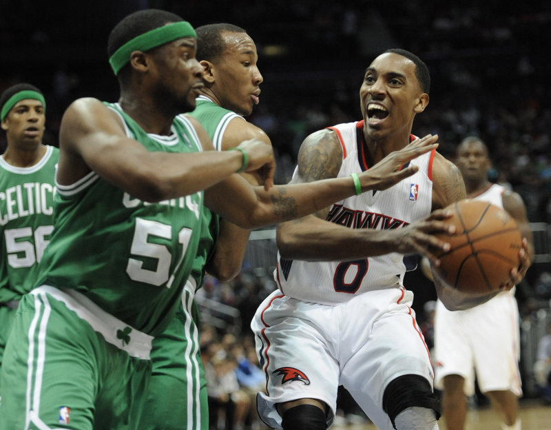 Atlanta's Jeff Teague is defended by Boston's Keyon Dooling (51) and guard Avery Bradley during the first half of Friday's 97-92 win for the Hawks. The Celtics fielded an unusual lineup after playing 11 games in 15 days.