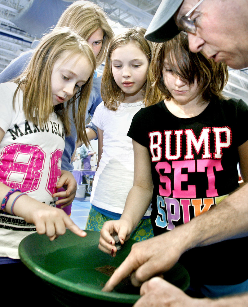 Bill White of Coos Canyon Rock points out flakes of gold to first-time panners Maggi Bradford, 10; Annika Thaler, 16, an exchange student living with the Bradfords; Sophie Sangster, 11, and Savana Bradford, 8, all of Raymond, at the 29th annual Gem and Mineral Show.