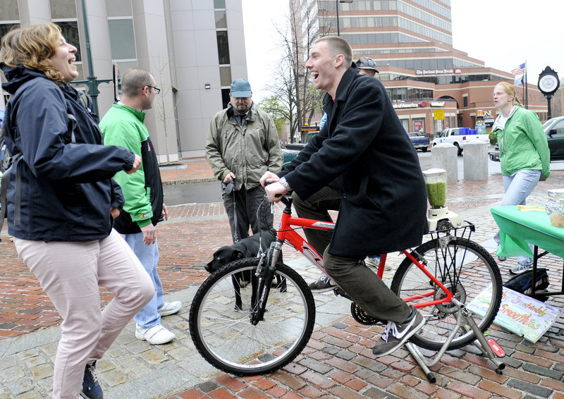 """Julie Carey, a direct support professional with Creative Trails, encourages Ray Borg of Portland to pedal a bike rigged to power a blender for making """"green"""" smoothies during the Urban Earth Day activities Sunday in Portland."""