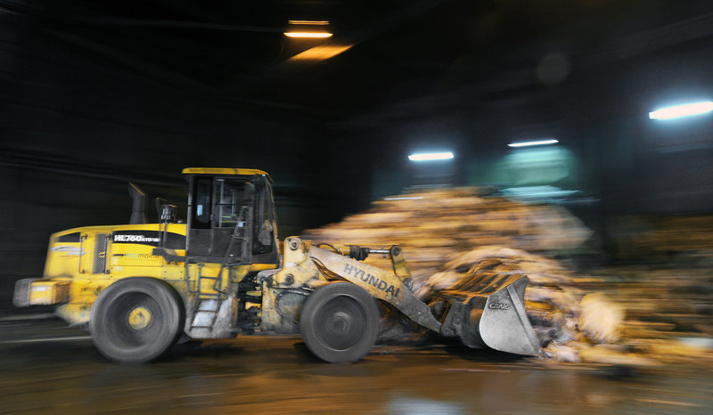"A bucket loader moves trash Monday into ""the bunker"" at ecomaine's processing facility in Portland. The plant, which opened in 1988, is owned and operated by 21 southern Maine communities."