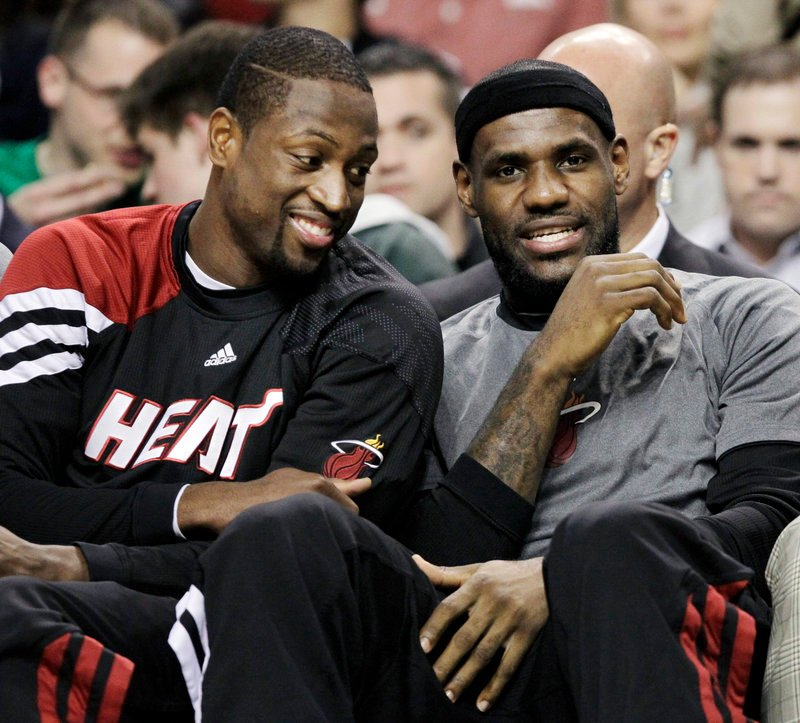 Dwyane Wade, left, and LeBron James spent the evening chatting on the bench Tuesday, spectators in a game neither team took seriously. Scoreboard said Celtics beat Miami.