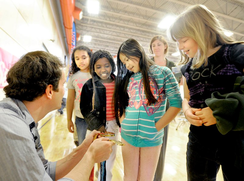 Seth Wescott shows his gold medals to Portland fourth-graders Sayvona Nelson, Sara Ali, Vy Diep and Bryanna Alley-Villers at the East End Community School.