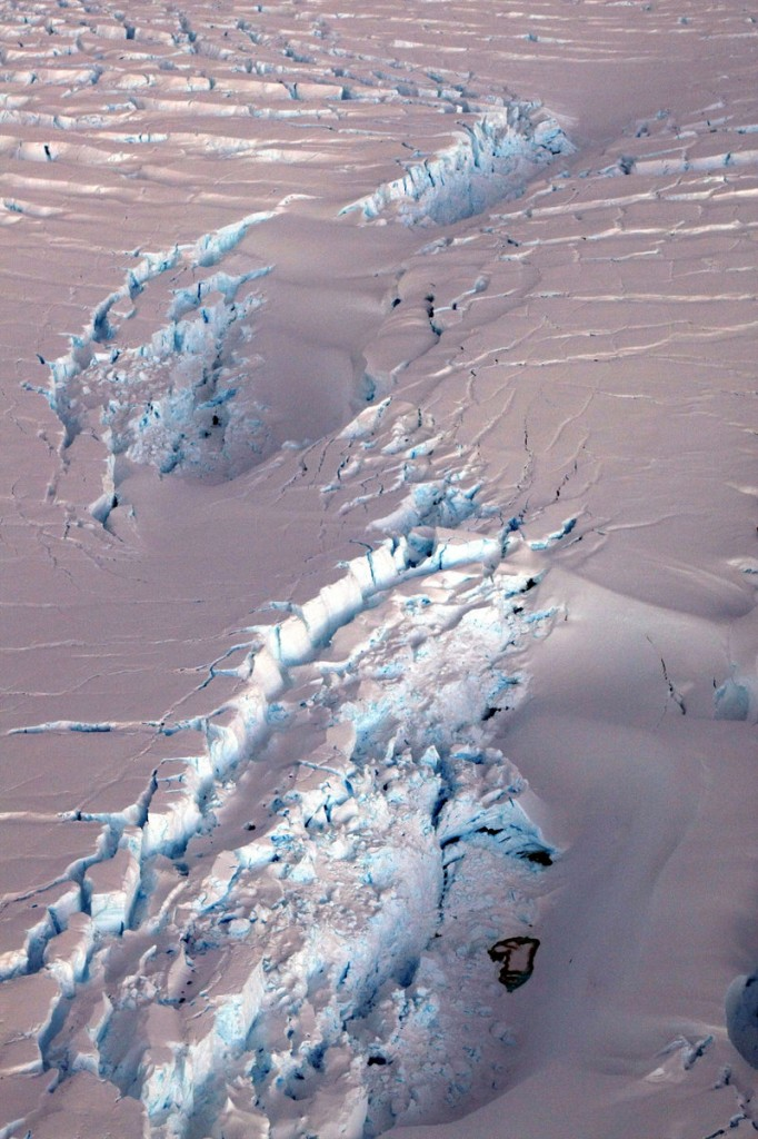 A deep crevasse forms in an ice shelf as an iceberg, left, breaks off. Research using an ice-gazing satellite, shows ice shelves are melting from warm water below, not just from warmer air. Wind current changes are pushing warmer water closer to and beneath the floating ice shelves.