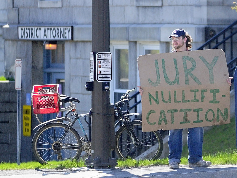 While a jury deliberates inside Thursday on the case of five Occupy protesters charged with trespassing at the Blaine House, a demonstrator holds a sign in front of Kennebec County Superior Court.