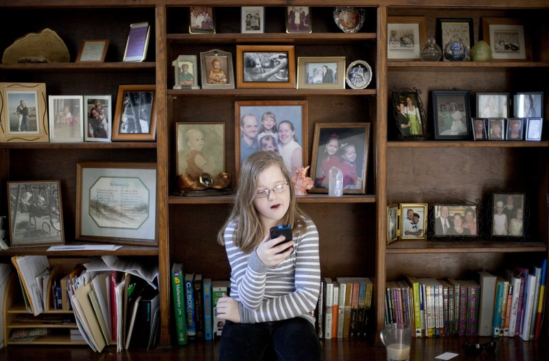 Alex Boston, 14, checks an email on a cellphone at home in Acworth, Ga. She has filed a libel lawsuit claiming two classmates humiliated her with a phony Facebook account.