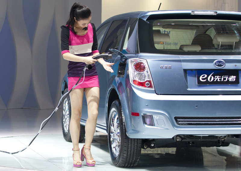 A woman demonstrates BYD Co.'s charging technology on an e6 electric car at the 2012 Beijing International Automotive Exhibition Monday. China has broadened its stated electric-car goals to include cleaner gas engines.
