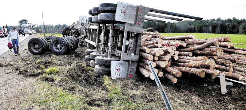 Driver Joseph Perrault, 30, of Norridgewock, walks past sheared-off axles and his pulp truck that rolled over and dumped logs near the intersection of Route 43 and the County Road in Madison in November 2011. Perrault escaped without injuries.