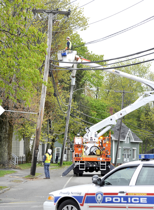A CMP crew works to repair a utility pole that was struck and split by a truck along Cumberland Street in Westbrook near Brown Street. Police blocked off that section to traffic as repairs continued.