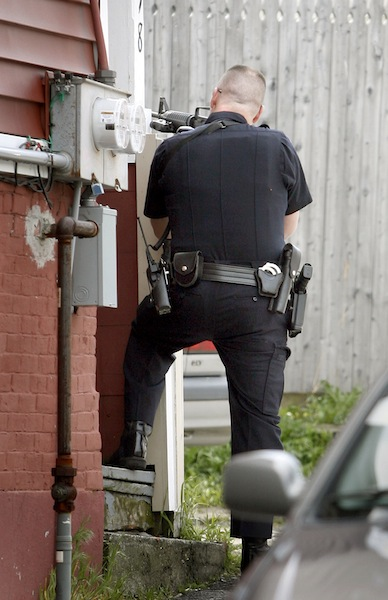 Portland Police Officer Kevin Haley on Oxford Street aims a gun at the back of 19 Cedar St.