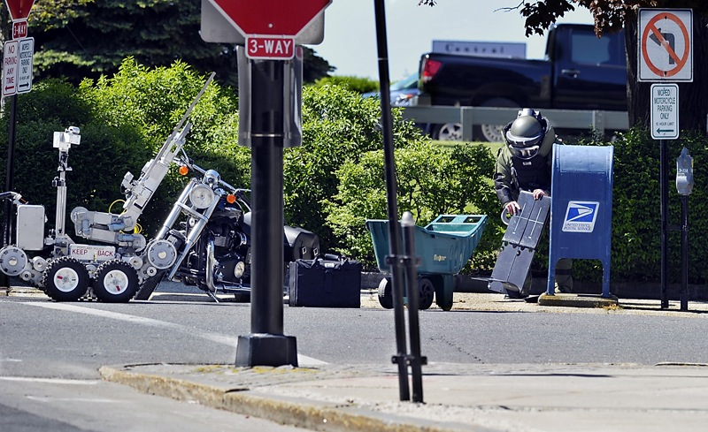 Preceded at the scene by a remote-controlled robot, Sgt. Frank Gorham of the Portland Police Department's Hazardous Devices Unit prepares to X-ray the contents of a mailbox at Market and Federal streets in Portland to determine the source of a suspicious beeping Saturday. Officials said the noise came from a cellphone inside a purse stuffed into the mailbox.