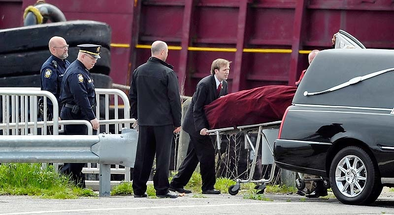 The body of Nathan Bihlmaier is lifted into the waiting hearse at a restricted portion of the Maine State Pier on Tuesday, May 22, 2012. The hearse took his body to Augusta for an autopsy.
