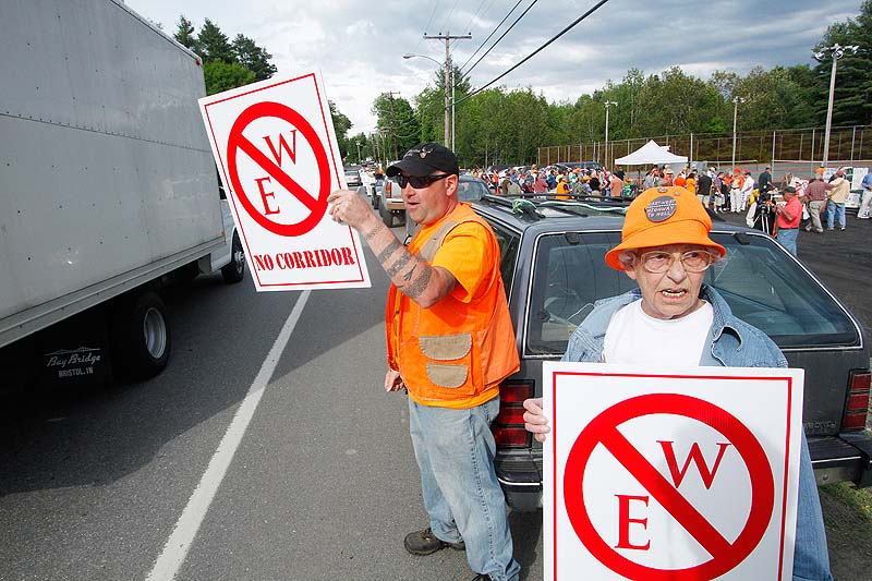 Rob Borden and Erla St. Pierre, both of Wellington, display signs in protest before a public meeting in Dover-Foxcroft concerning the proposed highway.