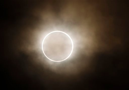 "The moon slides across the sun, showing a blazing halo of light, during an annular eclipse at a waterfront park in Yokohama, near Tokyo, Monday, May 21, 2012. Millions of Asians watched as a rare ""ring of fire"" eclipse crossed their skies early Monday. The annular eclipse, in which the moon passes in front of the sun leaving only a golden ring around its edges, was visible to wide areas across the continent. (AP Photo/Shuji Kajiyama)"