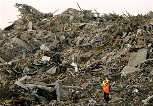 FILE- In this July 21, 2011 file photo, a worker walks among a pile of debris at a landfill in Galena, Kan., where some of the 2 million cubic yards of tornado debris have been hauled from nearby Joplin, Mo. Debris cleanup accounted for about one-fifth of the $500 million in tax dollars spent after an EF-5 tornado destroyed a large swath of Joplin last year. The tornado that tore through Joplin a year ago and already ranks as the deadliest twister in six decades, now is considered the costliest since at least 1950. (AP Photo/Charlie Riedel, File)