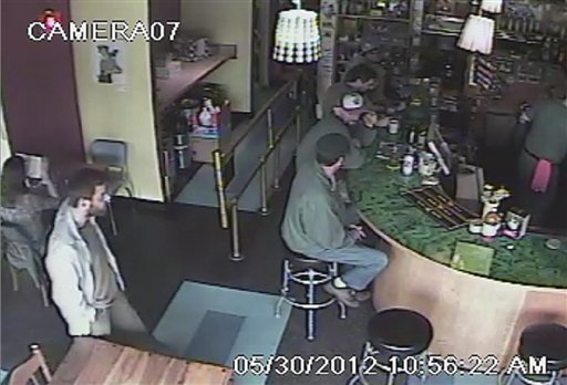 This frame grab provided by the Seattle Police Department shows a man believed to be the suspect in a shooting, left, at Cafe Racer on Wednesday in the University district of Seattle.