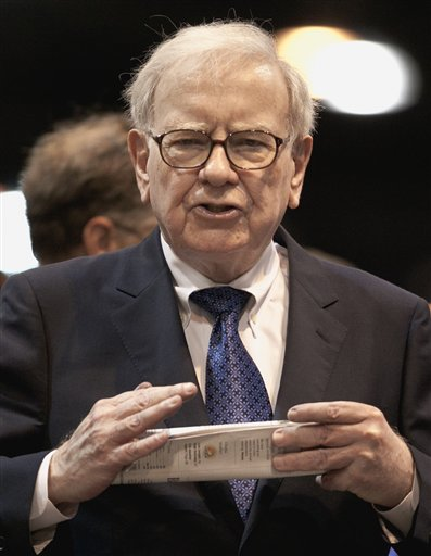 In this May 5, 2012, photo, Warren Buffett, chairman and CEO of Berkshire Hathaway, holds a newspaper at a shareholders meeting in Omaha, Neb.