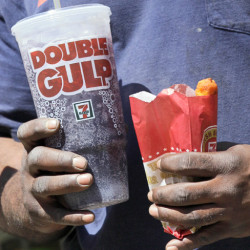 A man leaves a 7-Eleven store with a Double Gulp drink in New York today. New York Mayor Michael Bloomberg is proposing a ban on the sale of large sodas and other sugary drinks in the city's restaurants, delis and movie theaters in the hopes of combating obesity.