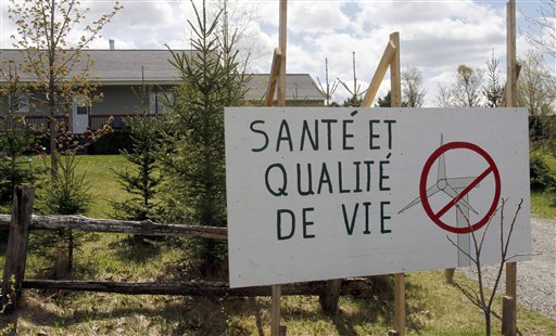 A Stanstead, Quebec, resident posts a sign opposing a Vermont wind development.