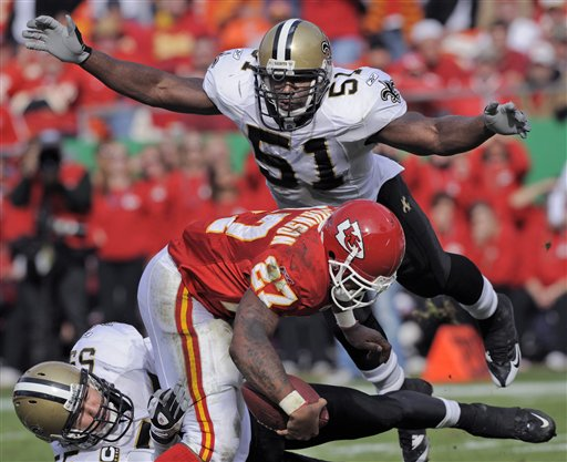 This Nov. 16, 2008, photo shows New Orleans Saints linebacker Jonathan Vilma (51) flying in to help stop Kansas City Chiefs running back Larry Johnson (27) as he's tied up by New Orleans Saints linebacker Scott Fujita, lower left, in a game in Kansas City, Mo.