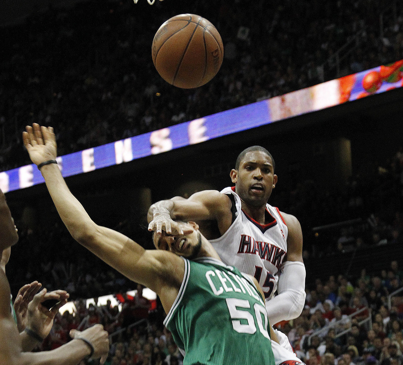 Atlanta Hawks center Al Horford and Boston Celtics center Ryan Hollins battle for a loose ball during the second half of Game 5 of a first-round playoff series game Tuesday in Atlanta. Atlanta won 87-86.