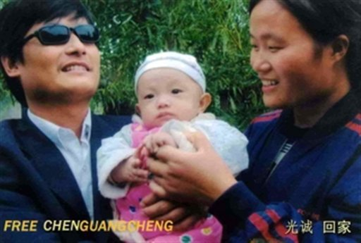 This undated photo provided by the China Aid Association shows blind Chinese legal activist Chen Guangchen, left, with his son, Chen Kerui, center, and his wife Yuan Weijing in Shandong province, China.